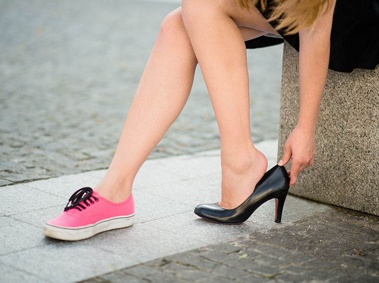 Girl wears one sneaker and one high heel