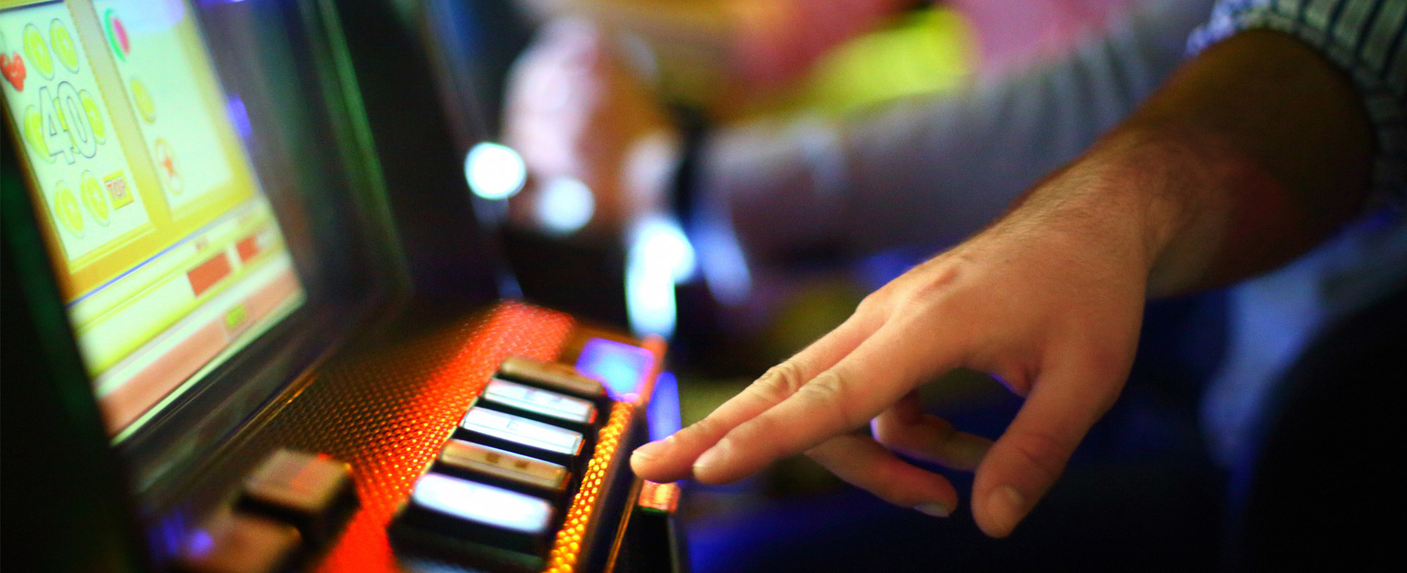 Close up of a man's hand about to press a button on a brightly-lit poker machine.