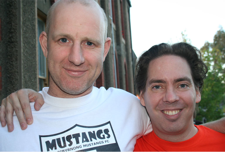 Photo of two smiling men with their arms around each other, the man on the right is shorter with dark hair, the man on the left has closely cropped blonde hair and is wearing a T-shirt that says: Mustangs, Maribyrnong Mustangs FC.
