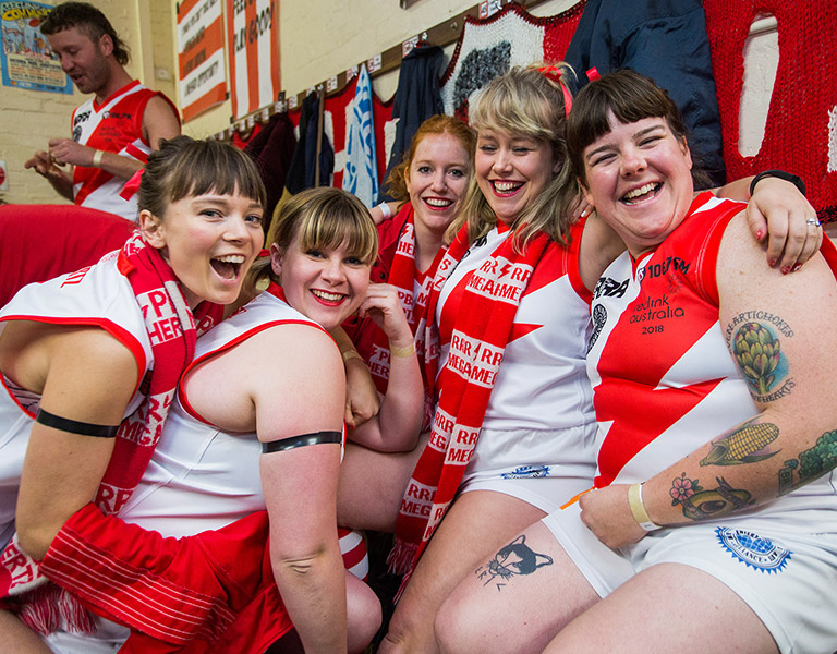 Five women in red and white football singlets sitting in a club change room with their arms around each other, laughing and looking at the camera, a man in a red and white singlet in the background.