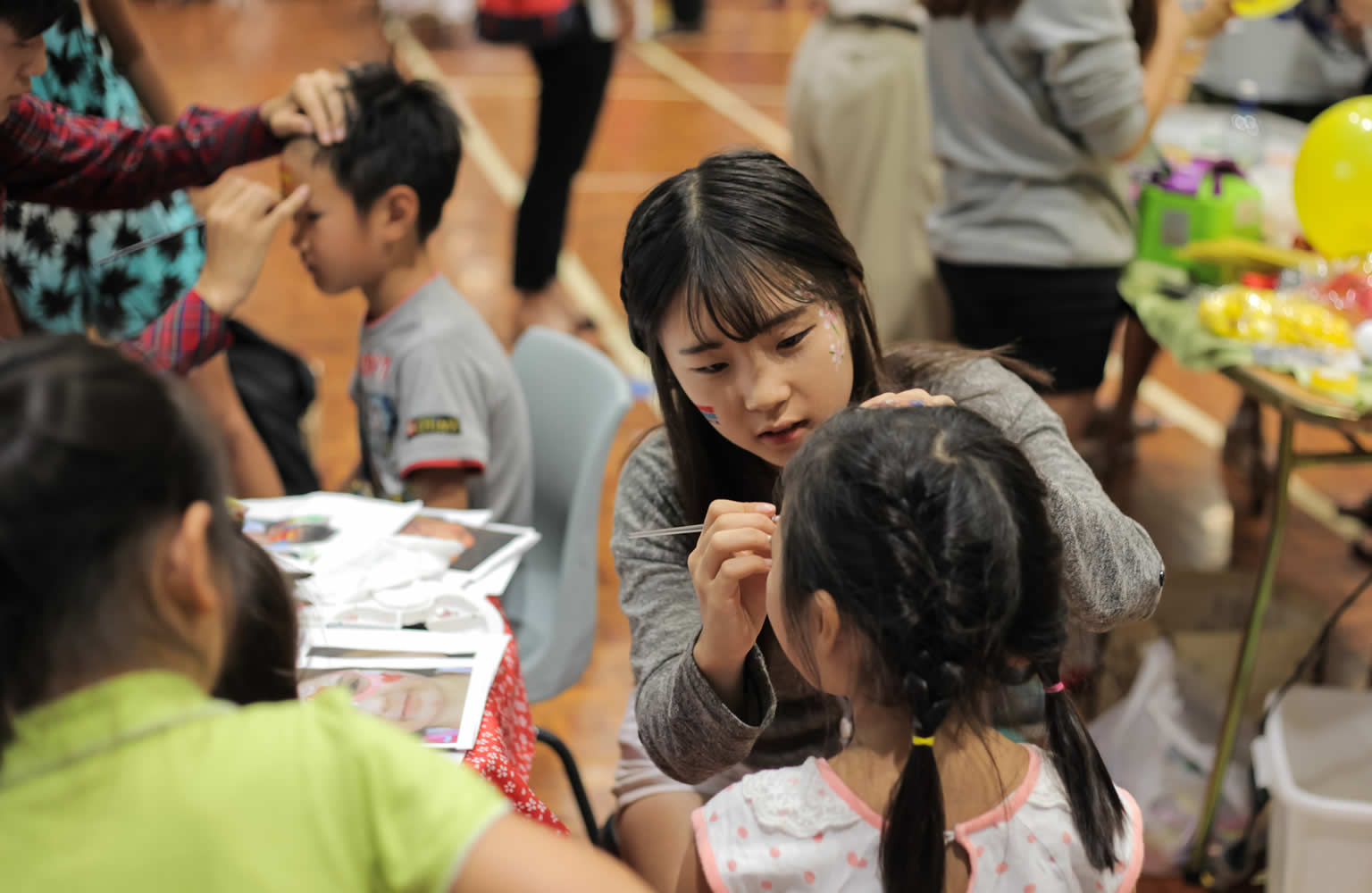 Korean volunteer Jooah Kang paints a child's face on New Zealand Korean Day 2015.
