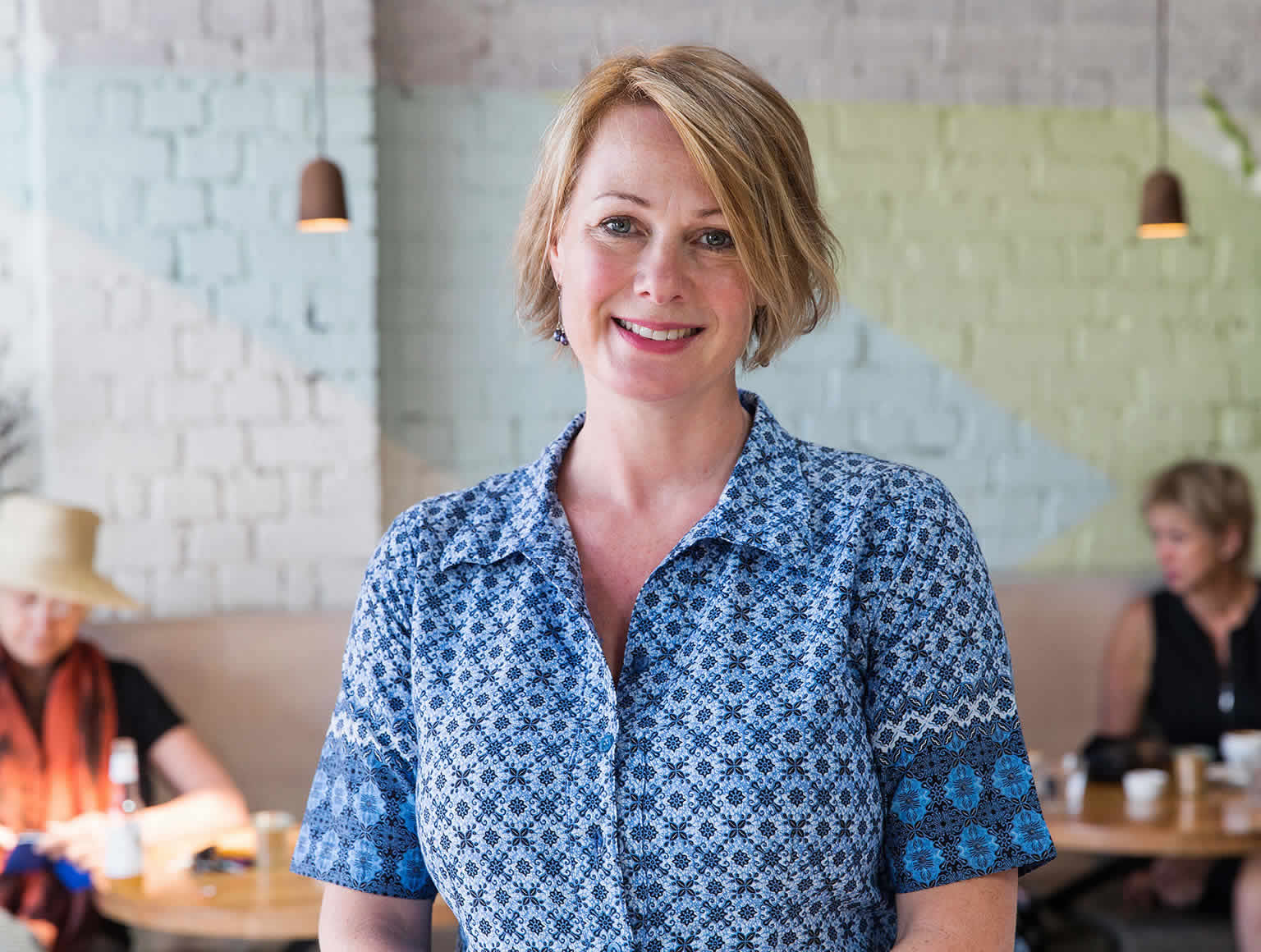 A smiling Jodi Clarke stands in a café in tables of diners on either side in background.