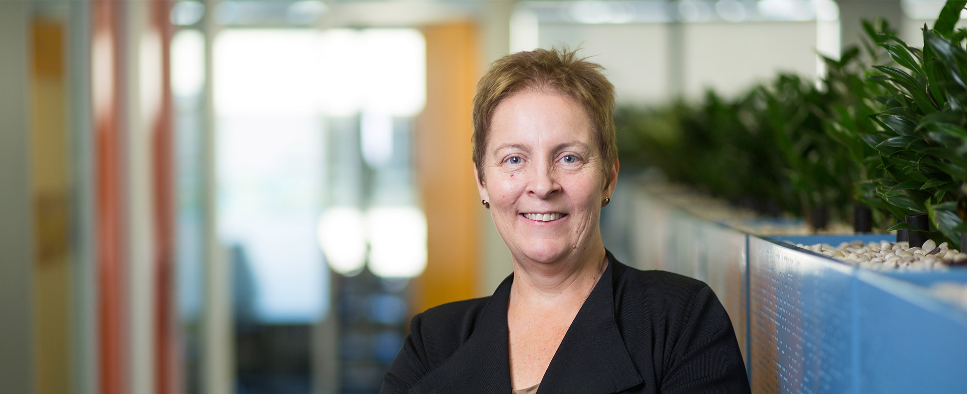 Headshot of Louise Glanville, Foundation CEO in front of a planter box, looking at the camera