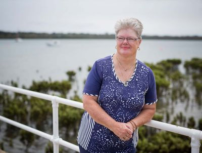 Photo of middle-aged woman with short fair hair wearing glasses and a blue and white T-shirt, standing smiling in front of a body of water, trees in the foreground, boats on the water, and bushland on the coast opposite