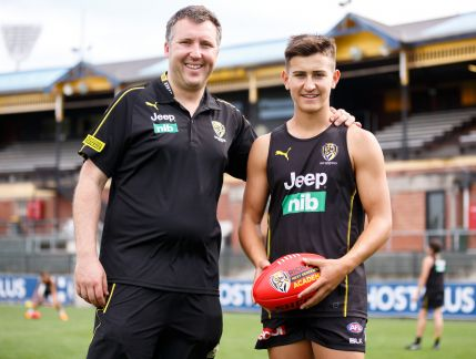 Photo of a middle-aged man in black Richmond Football Club casual wear with his arm across the shoulders of a teen boy in Richmond Football Club training singlet and shorts, both smiling at the camera while standing on the oval of a football stadium.