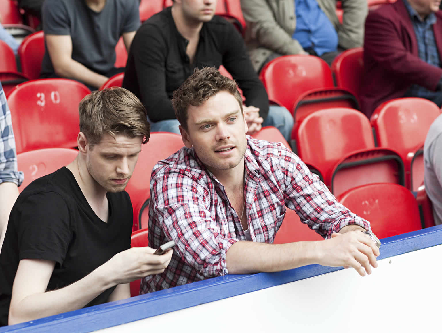 Two young guys on outside seating in a sports stadium, one watching game and the other looking at his mobile phone.