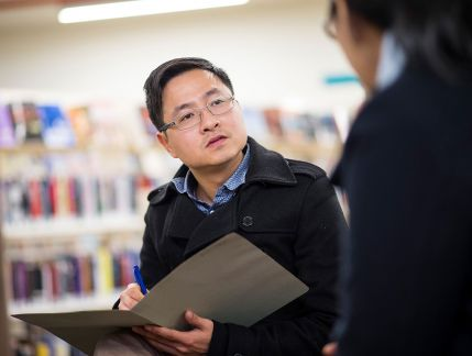 Photo of a man with short dark hair wearing glasses and sitting facing a woman in the foreground, whose back is to the camera. The man is holding an open folder and writing notes, shelves of books in the background.