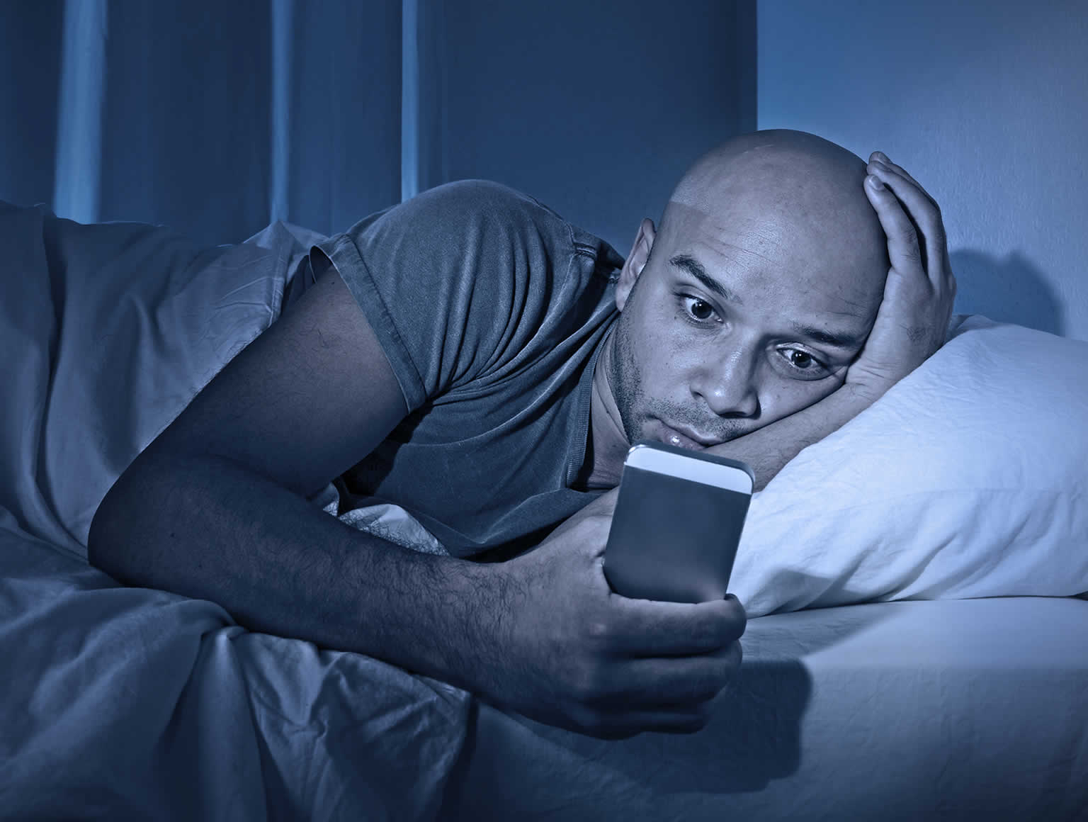 Man in bed at night looking at mobile phone screen.