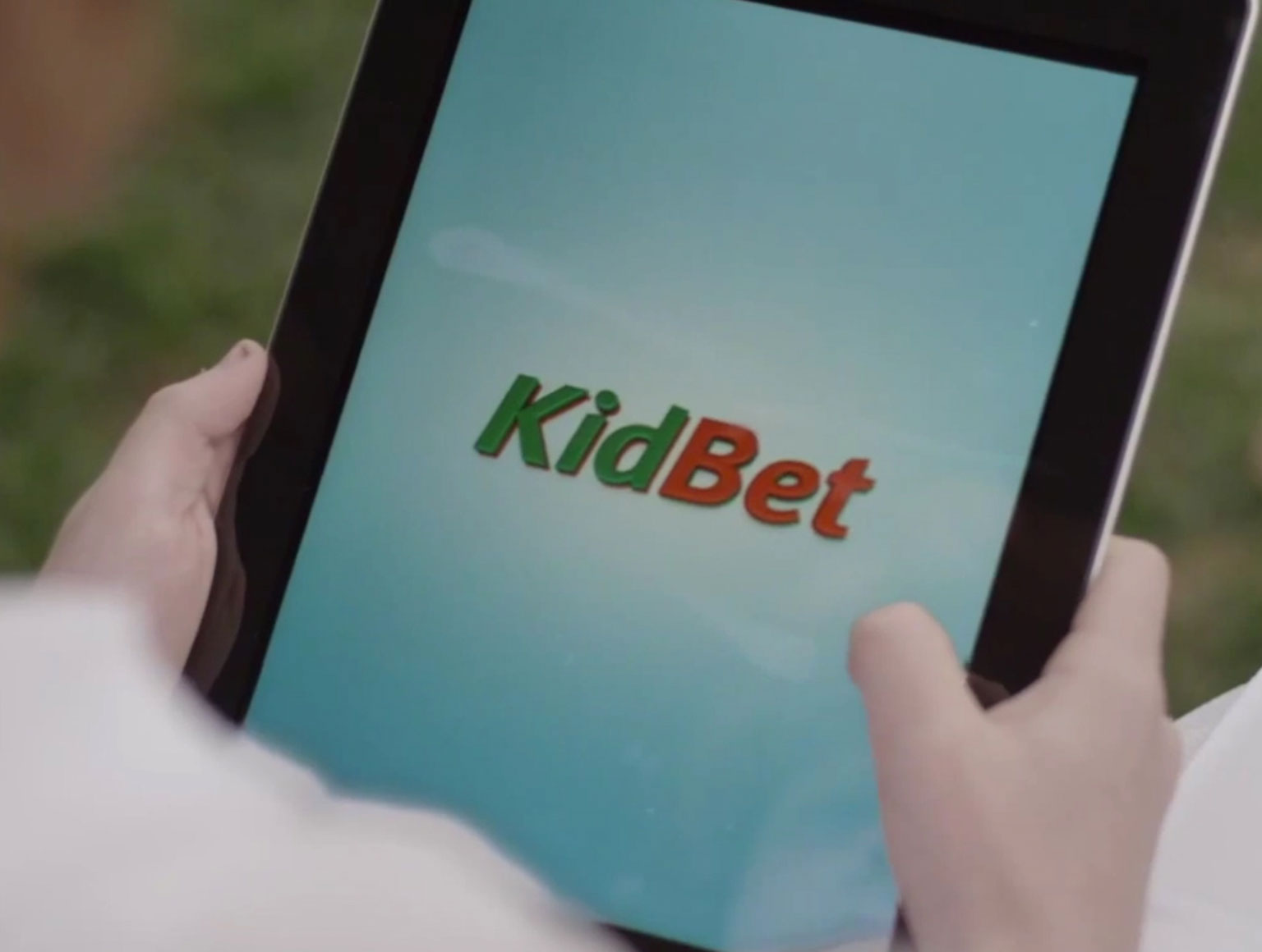 Boy holding tablet with blue screen showing 'KidBet' logo