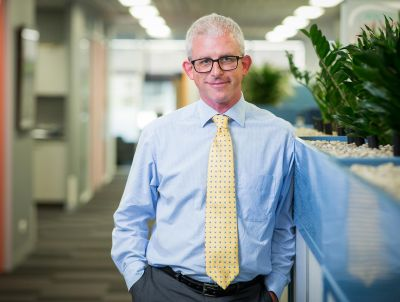 Photo of a middle-aged man wearing glasses, a blue business shirt and yellow tie standing beside plants in an office environment and smiling at the camera.