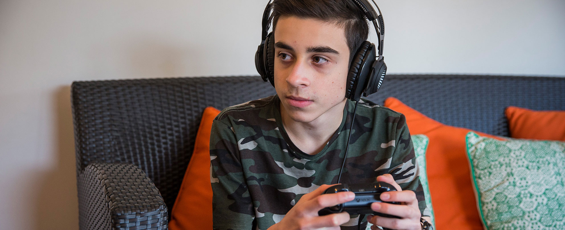 Photo of a teen boy in a camouflage t-shirt wearing headphones and operating the video game controller in his hands while sitting on a couch and looking off to the side, presumably at a screen where a video game is playing.