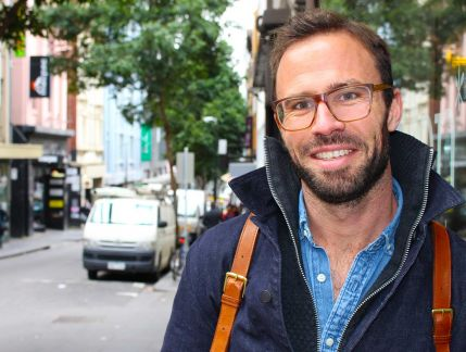Man in his 30s wearing casual blue winter clothing stands on the footpath of a narrow Melbourne street and smiles at the camera.