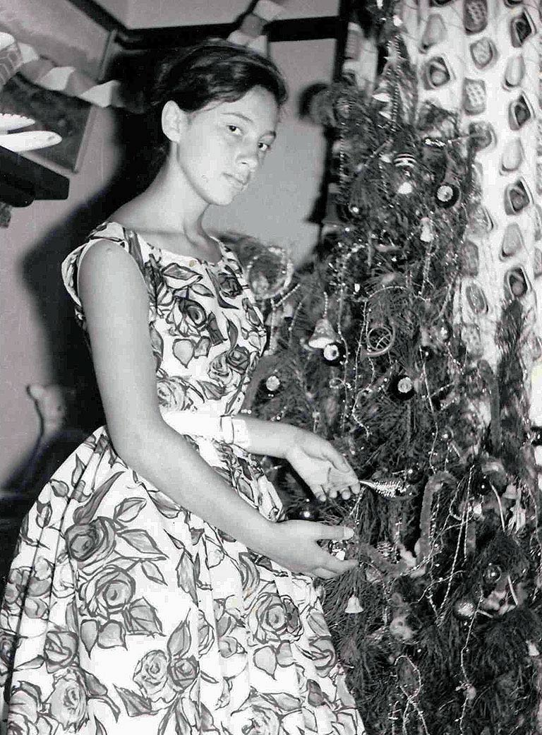 Black and white photograph of a young woman standing in front of a Christmas tree