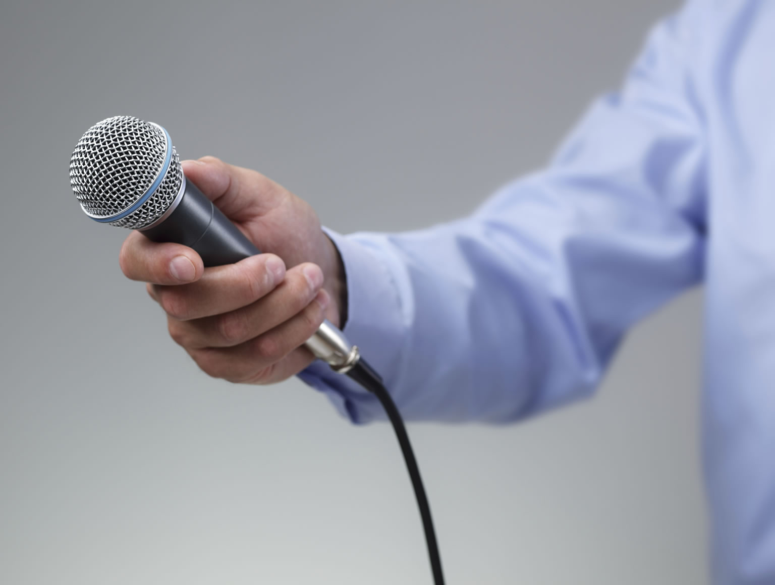 Man in a blue shirt against a plain background holding a microphone out as if awaiting a response
