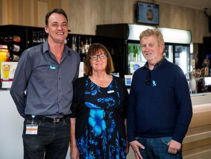Two men and a woman standing in front of a bar