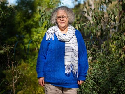 Photo of a smiling middle-aged woman with a grey curly bob wearing glasses, a blue jumper and blue and white striped scarf, standing in a native garden on a sunny day.