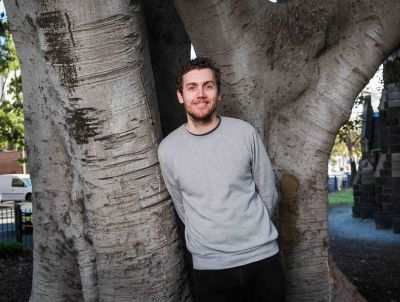 Daniel leans against a huge tree in a church yard and smiles at the camera