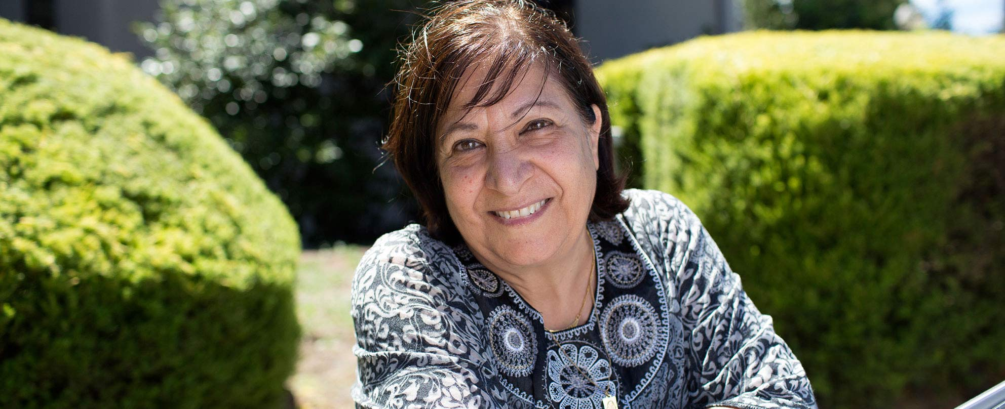 A smiling middle-aged woman sitting in a garden outside in the sun