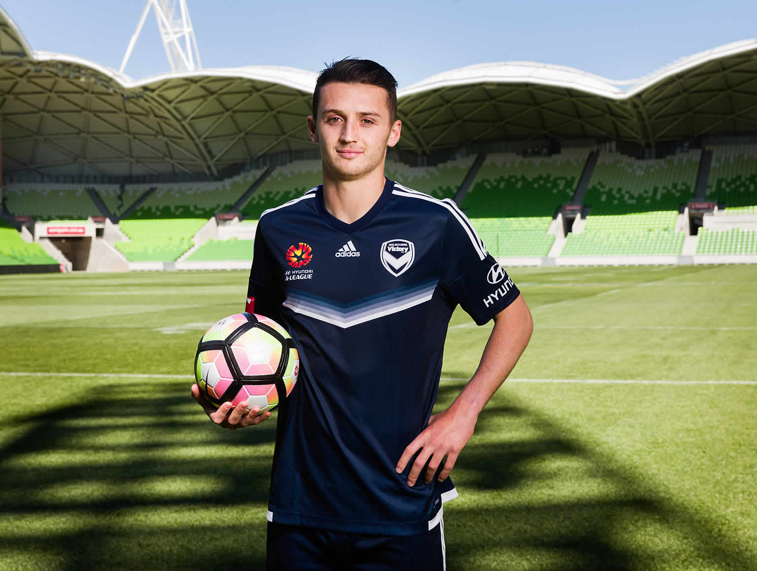 Melbourne Victory player George Howard standing on the field at AAMI Park with a ball