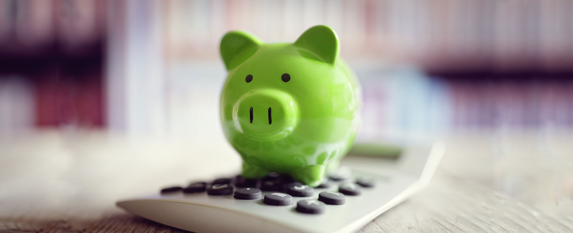 Close-up image of green piggy bank sitting on a calculator.