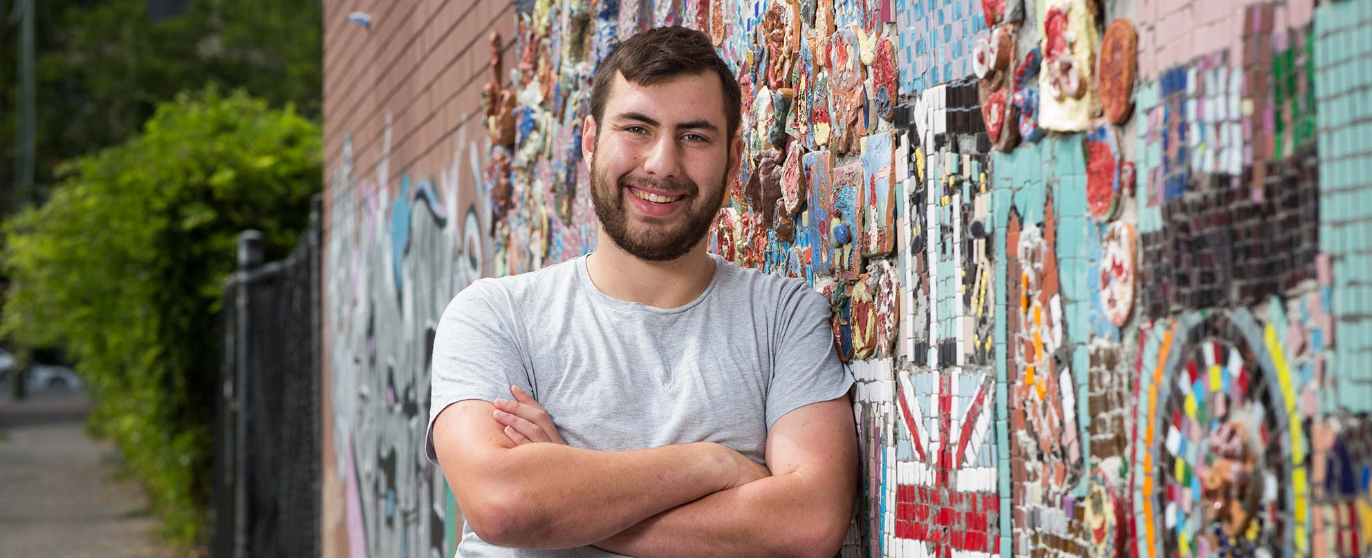 Photo of smiling young man with short brown hair and cropped brown beard, wearing a grey T-shirt, leaning, arms folded, against a brick wall with colourful mosaics adhered to it, a path and trees in the background.