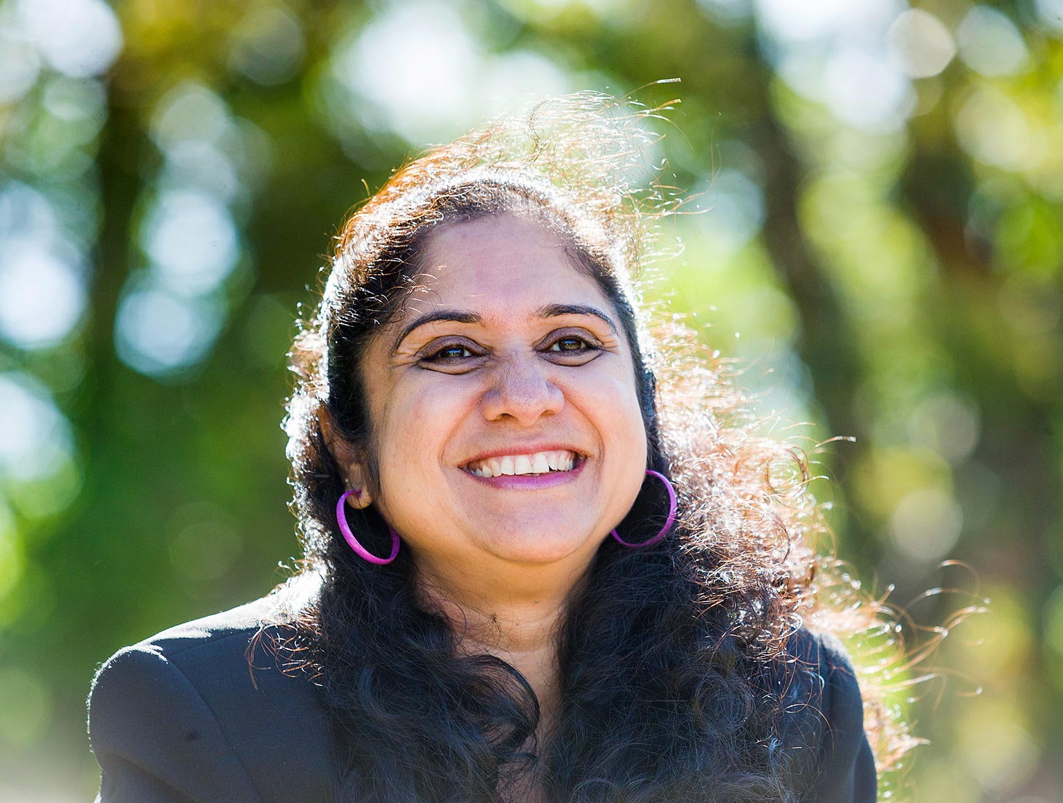 Chandana Rao smiling whilst sitting outside in the sun with a background of tall trees.