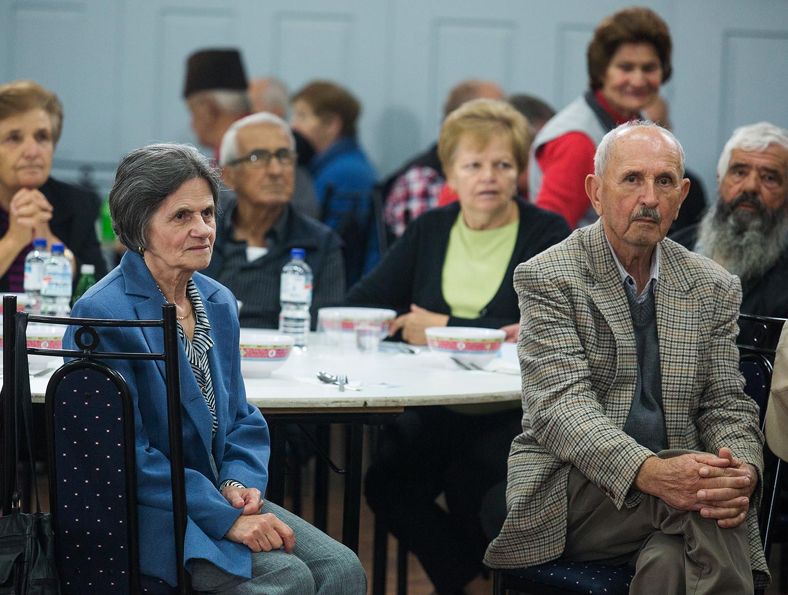 Photo of six older people sitting at a round table as part of an audience, watching a point behind the camera, other audience members sitting at tables in the background.