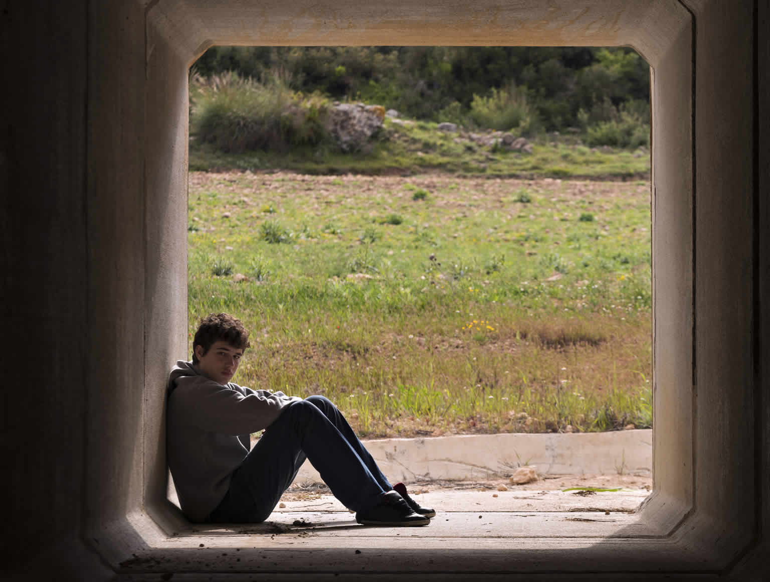 Teenage boy sitting alone at in a large tunnel.