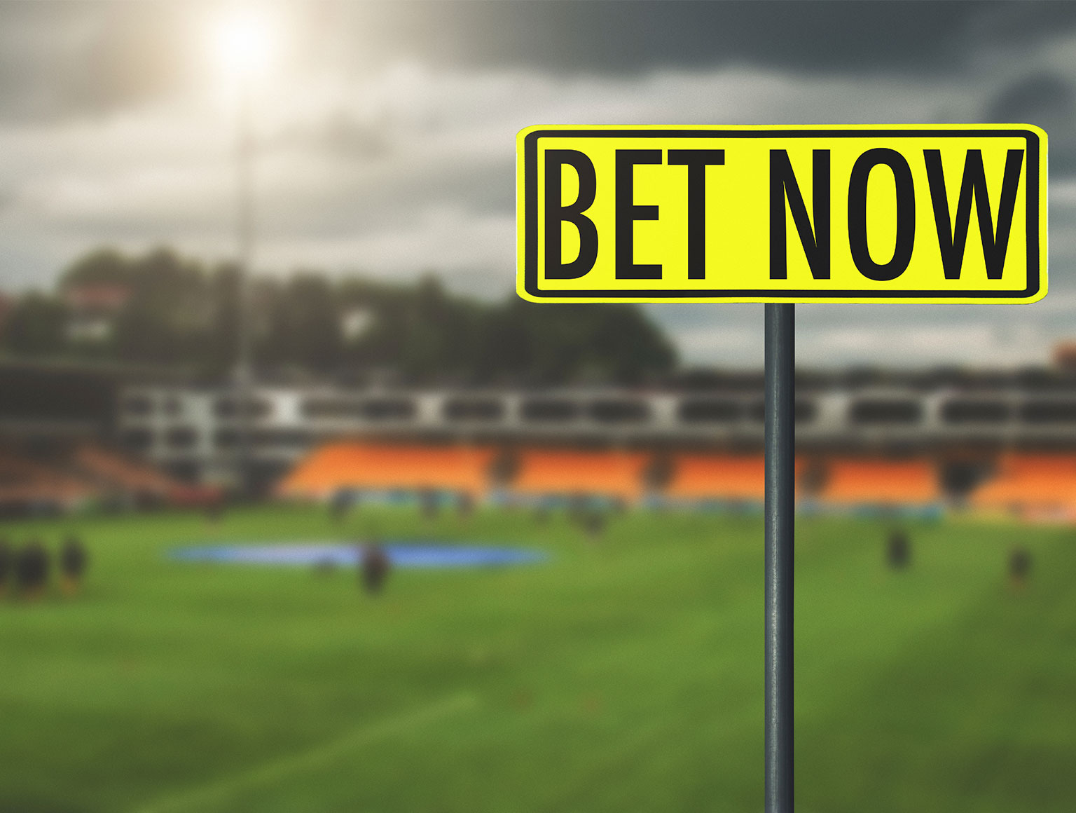 Prominent sign in foregound saying 'Bet now' and blurry sports field in background