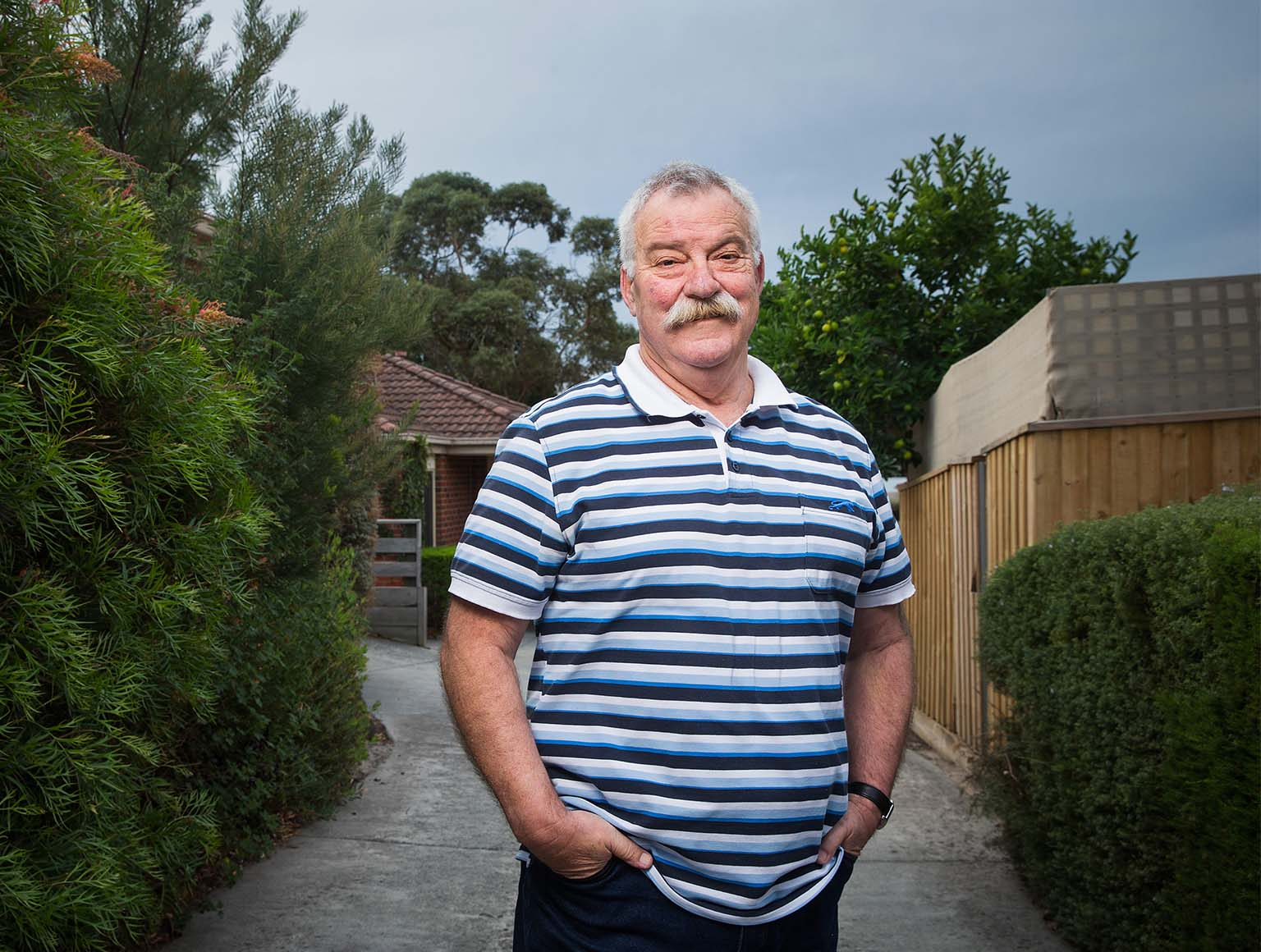 Photo of an older man with short grey hair and a grey moustache, wearing a blue and white striped polo shirt, standing in a suburban driveway, hands in pockets, smiling at the camera.