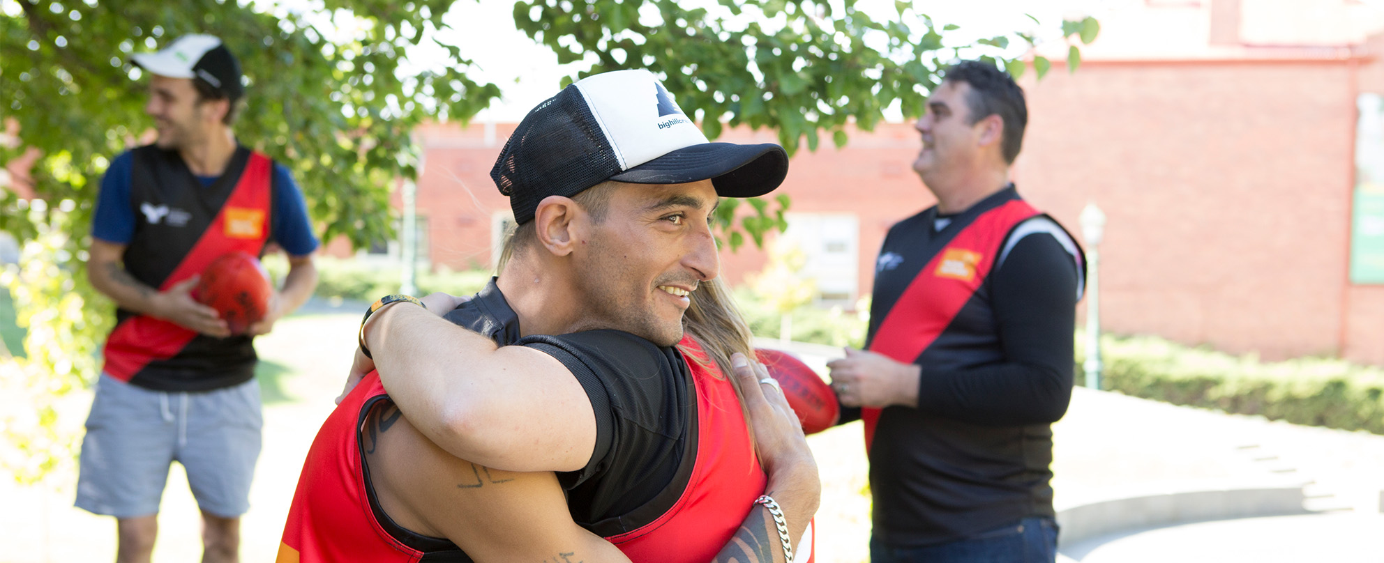 Photo of a young man in a cap hugging a young woman outdoors on a sunny day, two other young men in the background, one holding a football - all are wearing black and red football guernseys.