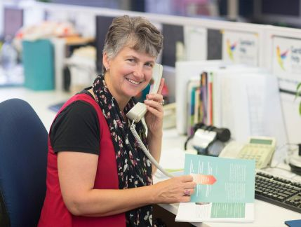 Photo of middle-aged woman with short grey hair on a landline phone at her workplace desk, smiling at the camera