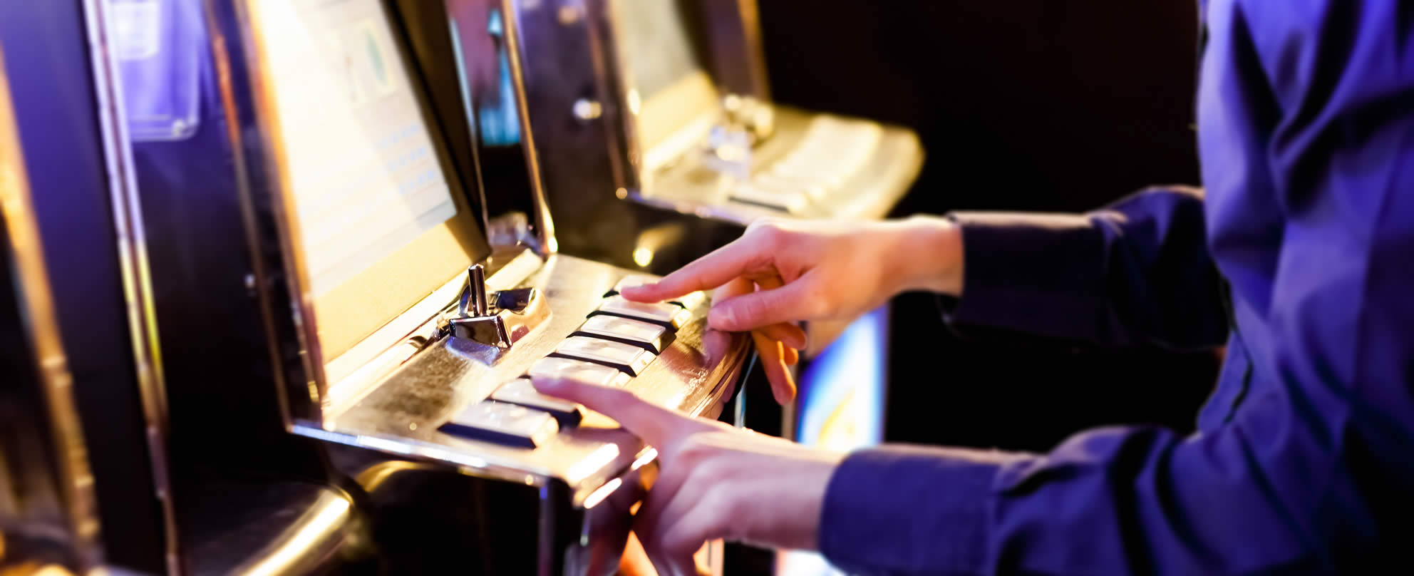 Man in a gambling venue with his fingers on the buttons of a pokie machine