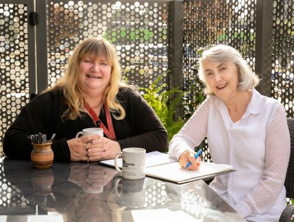 Photo of two seated women smiling at the camera, one wearing black and the other wearing white, sharing a cuppa at a table in an outdoor setting with a large exercise book open between them.