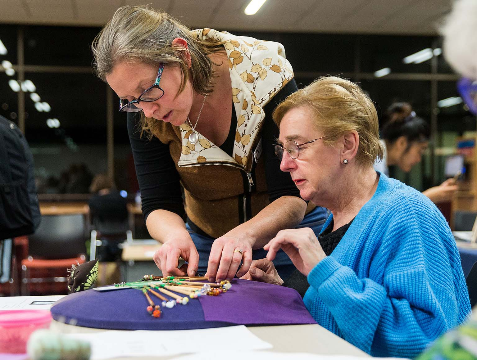 Photo of a middle-aged woman standing beside a seated older woman, showing her how to thread lace using bobbins on the table in front of her, other women in the background, nightime outside the window.