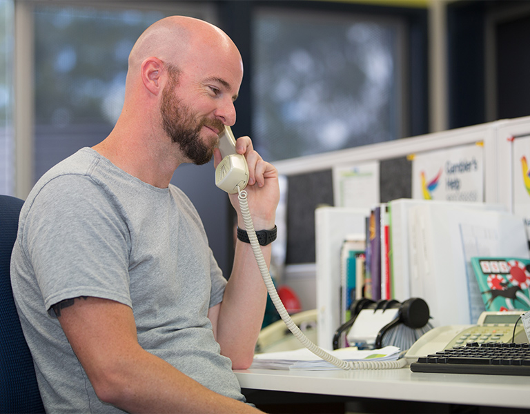 Photo of a man in his thirties with a shaved head and beard, sitting at his workplace desk, smiling and listening on a landline phone