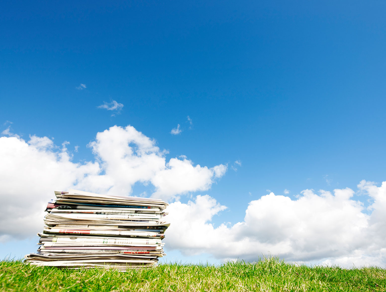 Newspapers on grass with blue sky background