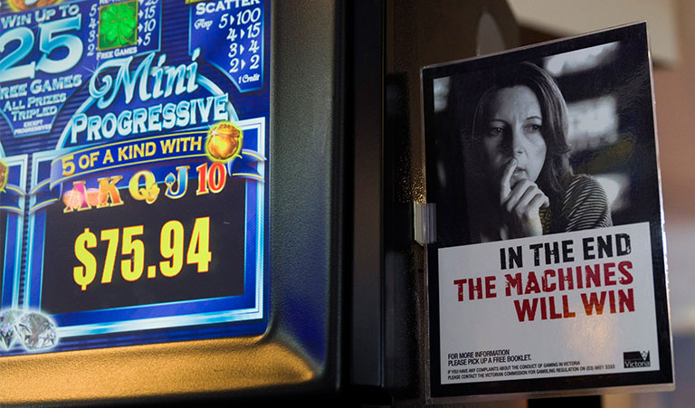 Close up of poker machine with gambling warning message on the side