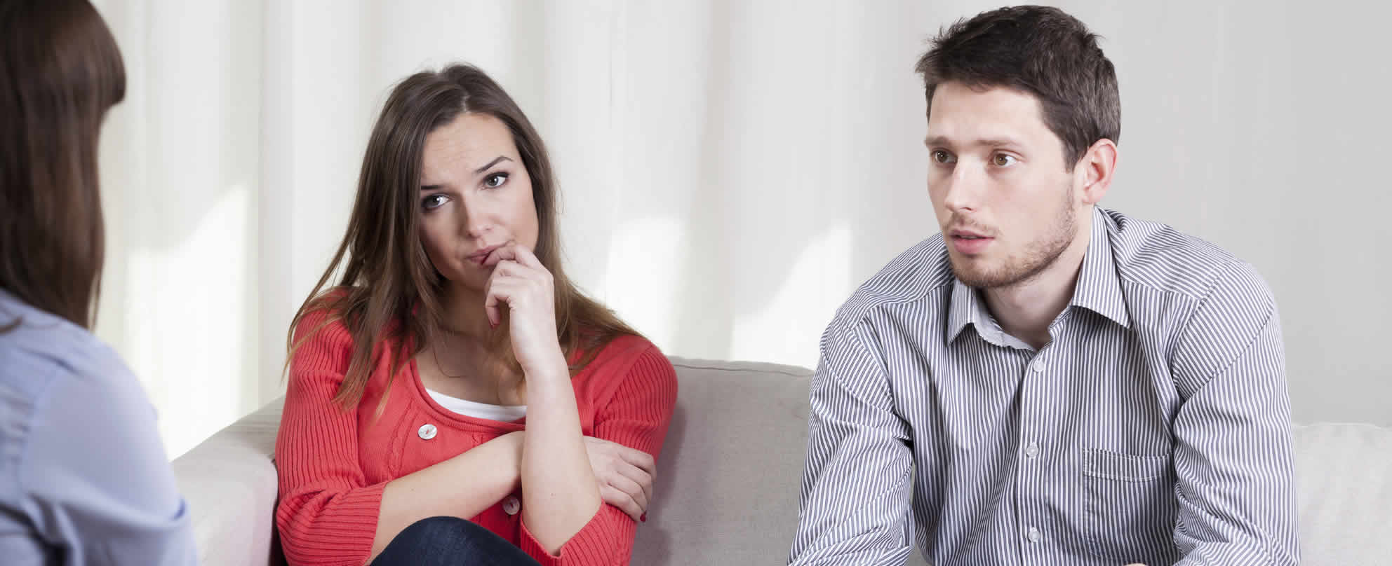 Young couple sitting on sofa, looking towards and listening to counsellor.