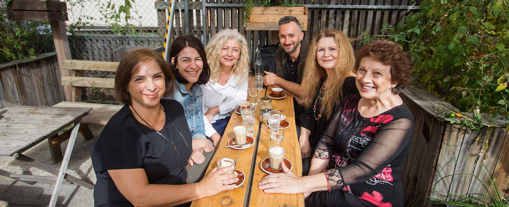 Photo of five middle-aged women and a slightly younger man, all smiling, having coffee at a courtyard table at a cafe