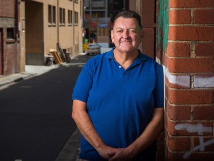 Photo of a middle-aged man leaning against a brick wall, smiling, a sunlit city alley behind him