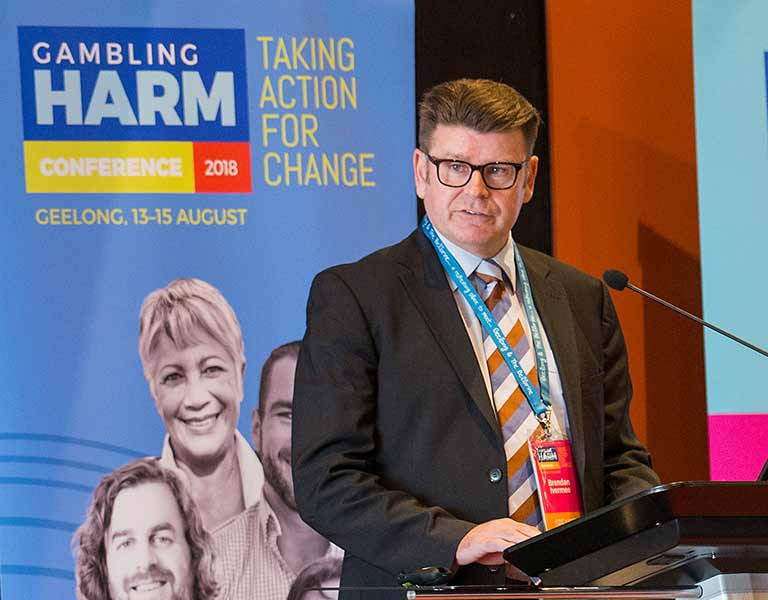Photo of a man with short brown hair and glasses speaking into a microphone at a lectern, a banner behind him says: Gambling Harm Conference 2018, Geelong 13-15 August, Taking action for change.