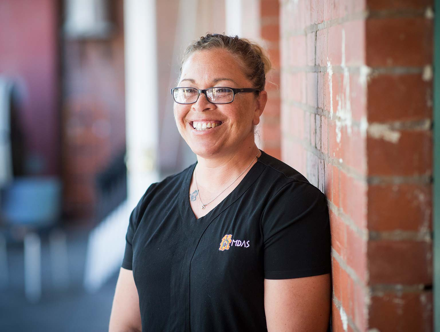 Photo of smiling woman with hair pulled back tightly and wearing glasses and a black T-shirt with an MDAS logo on it, she is standing outside against a red brick wall.