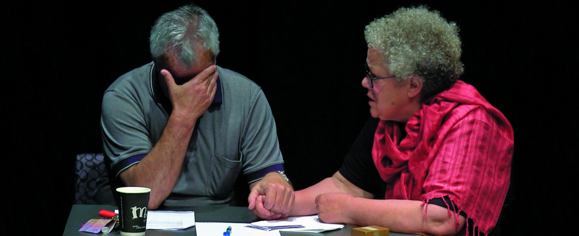 A woman sits at a table comforting a distressed man in a scene from the theatre performance of 'Three Sides of the Coin'