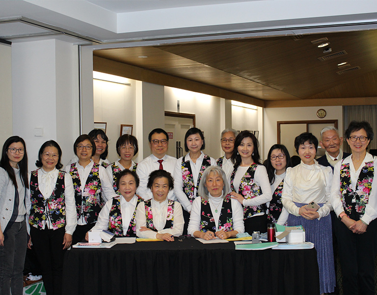 Photo of 14 women and two men, smiling and sitting or standing behind a black reception table, most of the women are wearing white shirts and black waist coats with a floral print.