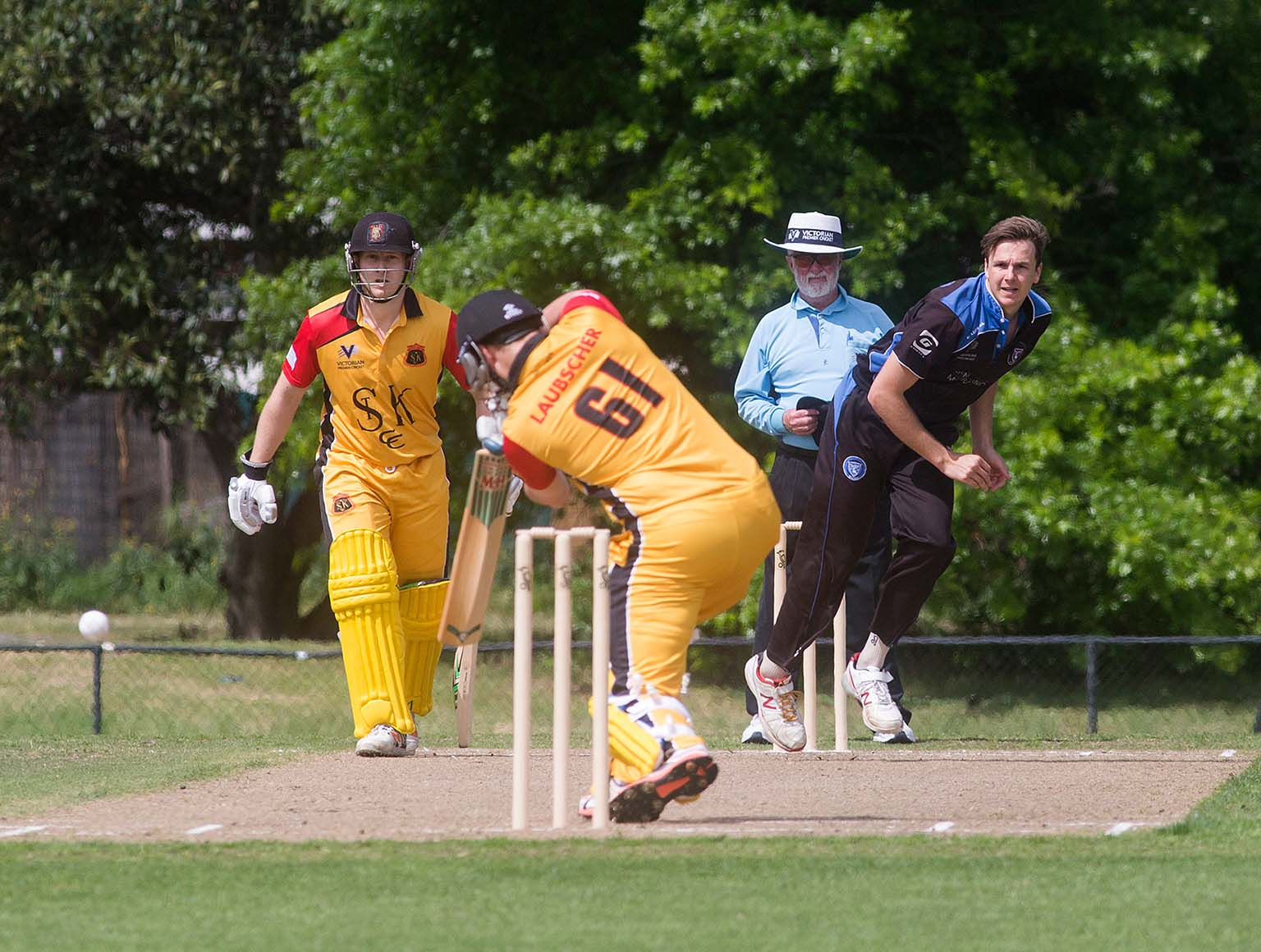 An action shot showing two batsmen, a bowler and an umpire at a cricket match