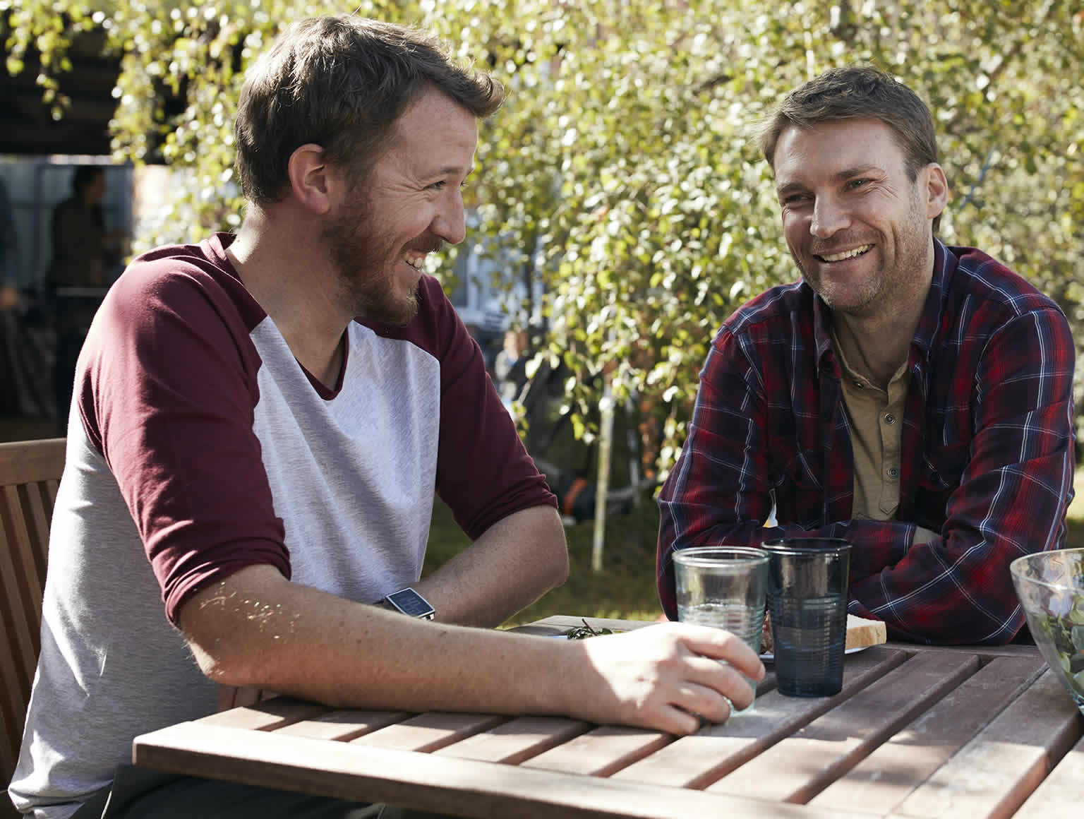 Two mates sitting at a table outside in a leafy garden during a friendly bar-b-q on a sunny day. There are drinks and food on the table and two women are standing up chatting away from the table