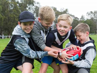 Young players from the Ivanhoe Junior Football Club with a footy on the playing field
