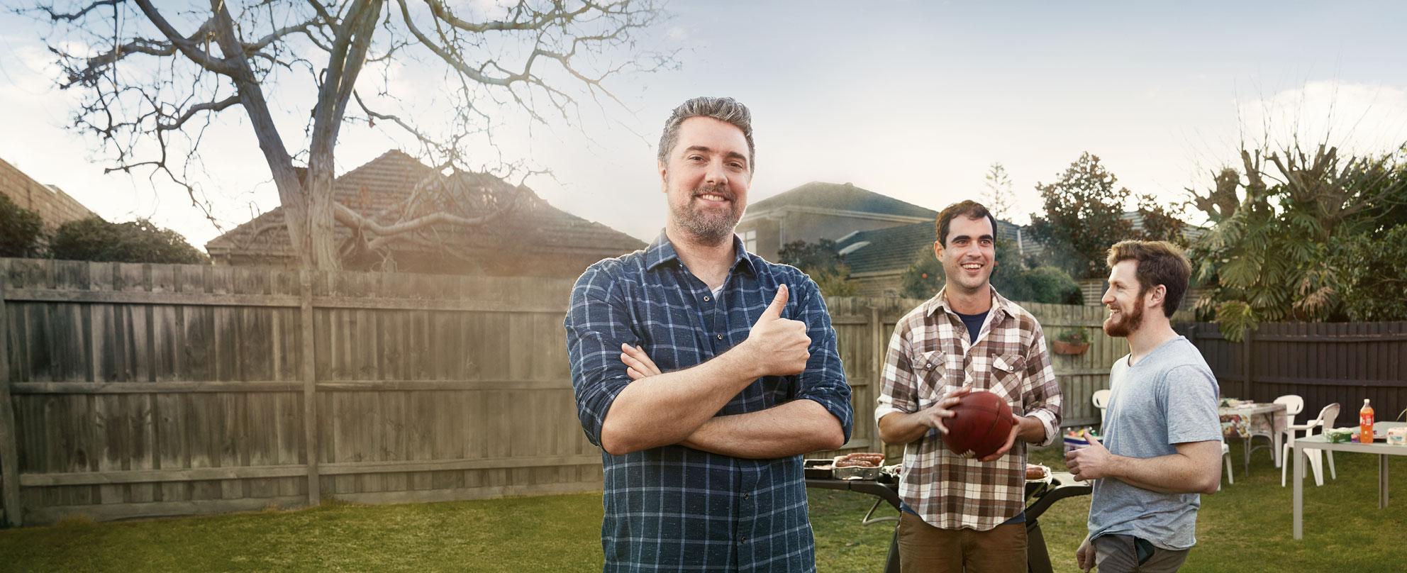 Three men at a barbeque in a suburban backyard - one man in the foreground giving the thumbs-up, while the two others chat in the background, one holding a football