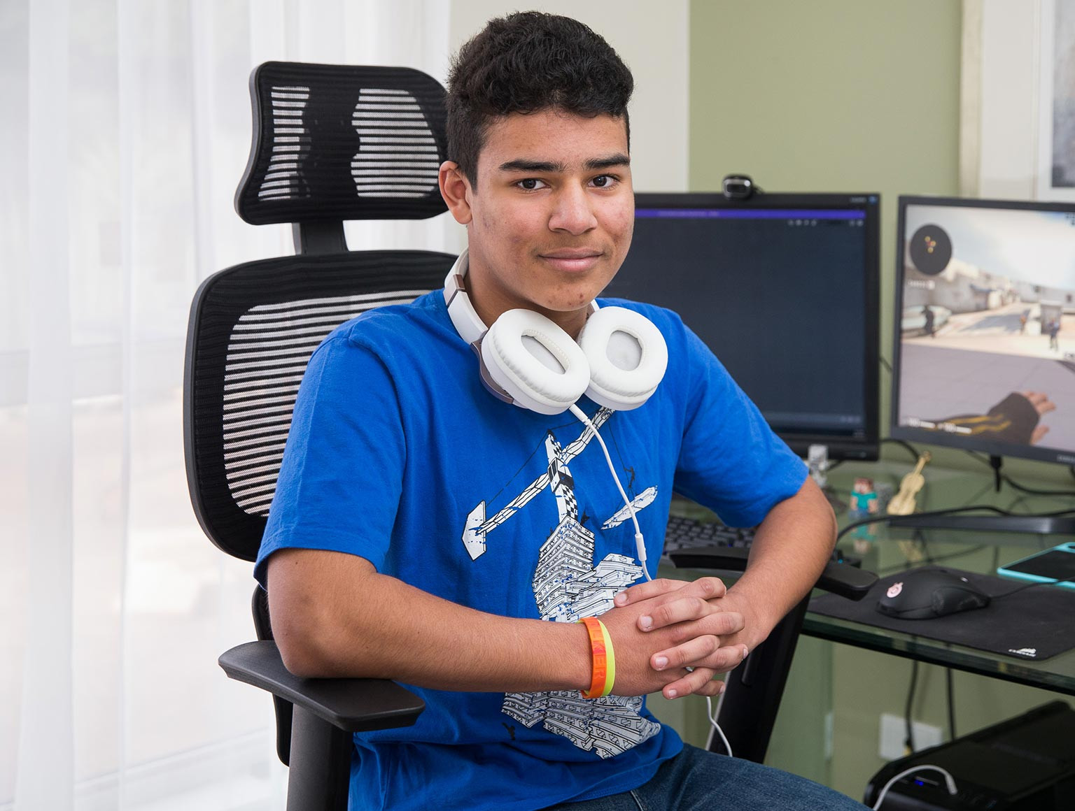 Photo of a smiling teenage boy with short dark hair wearing a blue T-shirt and head phones around his neck, sitting at a desk on which there are two computer screens, one with a video game displayed.